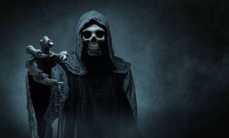 Grim reaper che raggiunge la telecamera su sfondo scuro con spazio di copia Archivio Fotografico