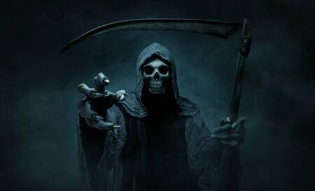 Grim reaper reaching towards the camera over dark, foggy background with copy space Фото со стока