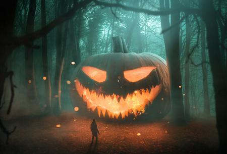 Abstracte Jack 'o Lantern-pompoen in het donkere bos 's nachts Stockfoto