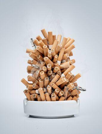 Aschenbecher voller Zigaretten isoliert auf grauem Hintergrund mit Kopierraum Standard-Bild