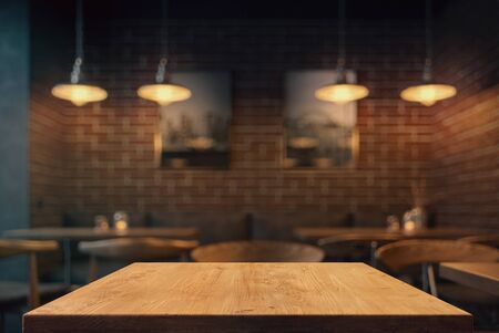 Empty tabletop in the coffe shop at night over defocused background with copy space
