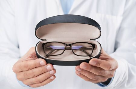 Close up of doctor oculist, optometrist holding, giving new eyeglasses Stock fotó