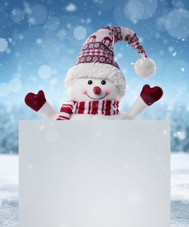 Happy snowman in the winter scenery behind the blank advertising banner with copy space