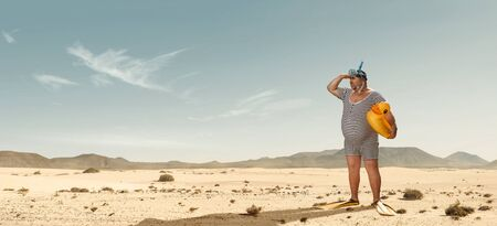 Funny overweight swimmer looking for the beach  in the middle of the desert with copy space Stock fotó