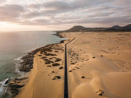 Aerial view of an empty road through the dunes at the sunrise with copy space