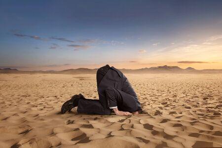 Uomo d'affari disperato che nasconde la testa nella sabbia nel deserto con spazio di copia
