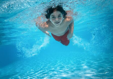 Portrait d'un mignon petit garçon nageant dans la piscine avec espace de copie Banque d'images