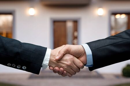 House selling concept. Two people handshake in front of the new house with copy space