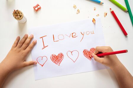 High angle view of childs hands drawing I love you sign on the paper sheet