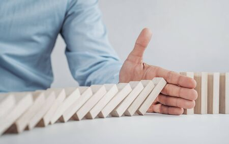 Close up of businessman stopping the domino effect on the wooden blocks with copy space