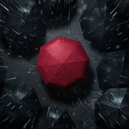 Standing out from the crowd, high angle view of red umbrella between many dark ones in the rain