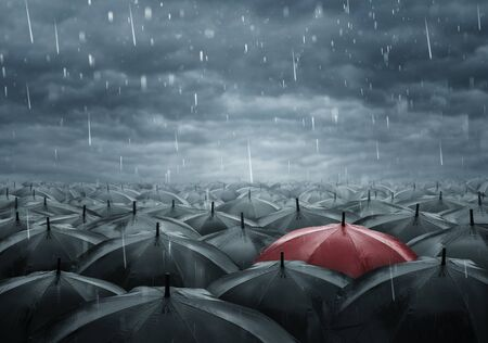 Standing out from the crowd concept, single red umbrella between many black ones on a rainy day 版權商用圖片