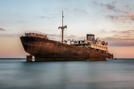 Shipwreck at the sunset on a Lanzarote coast with copy space 版權商用圖片