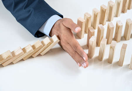 Close up of businessmans hand stopping the domino effect on the wooden blocks with copy space