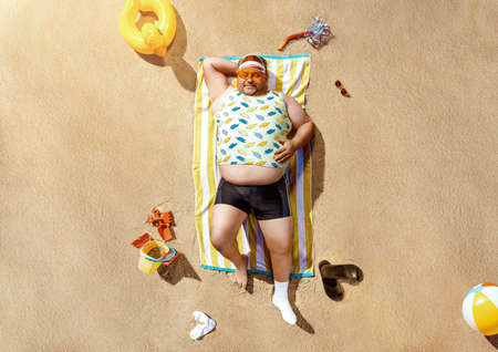 High angle view of funny overweight tourist resting on the beach 版權商用圖片