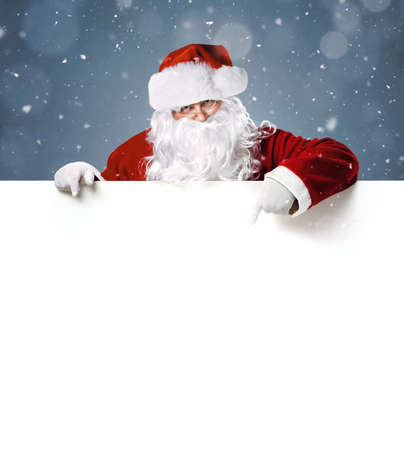 Happy Santa Claus pointing in blank white advertisement banner with copy space 版權商用圖片