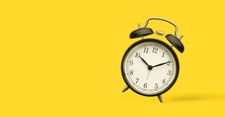 Close up of alarm clock isolated on yellow background with copy space