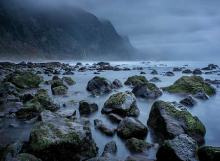 Nature background, stones on the seashore at the rainy evenng with copy space