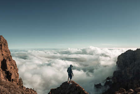 Man standing on the mountain peak above the clouds 版權商用圖片