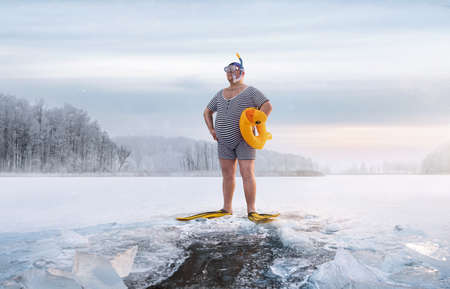 Fuunny overweight, retro swimmer standing by the ice hole in the lake, at the cold sunrise with copy space