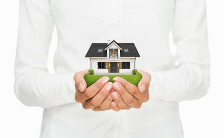 Property insurance concept, close up of female hands holding small house