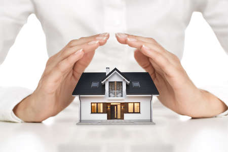 Home protection concept, close up of female hands covering modern house 版權商用圖片