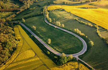 Aerial view of a curvy road through the Masurian landscape at the sunset