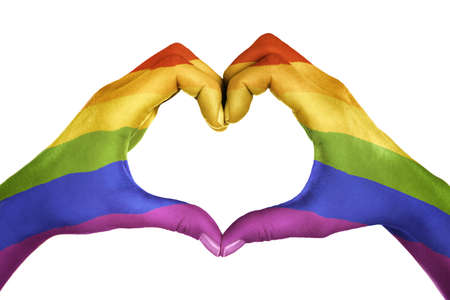 Female hands, painted in the LGBT flag, forming heart shape isolated on white background