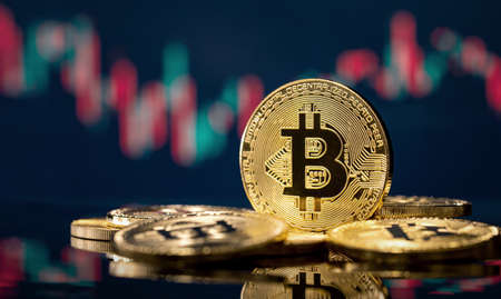 Golden bitcoin coin over defocused stock chart with copy space Archivio Fotografico