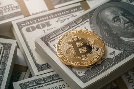 Shiny golden bitcoin coin over dollar bills background with copy space