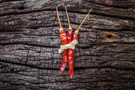 Dry chili peppers are placed on old wood.