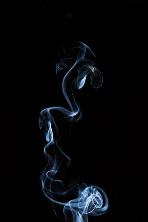 black textured background: Bizarre shapes of incense smoke on a black background.