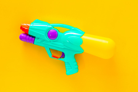 Plastic water gun isolated on yellow background