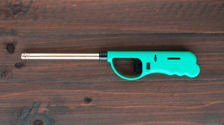 Gas lighter gun for gas-stove on a wooden background