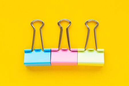 Colorful paper clips on a yellow background
