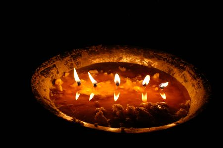 metall lamp: close-up picture of a Tibetan butter lamp in a dark temple Stock Photo
