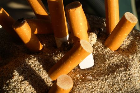 injurious: Several cigarette stumps sticking in an ashtray filled with sand Stock Photo