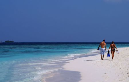 Beach pleasure: Man and woman with snorkeling gear walking on a tropical beach Imagens