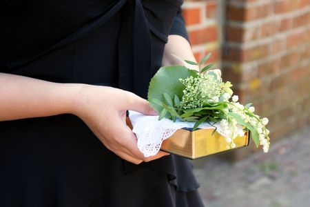 female confirmand holding flowers and hymn-book Stock Photo