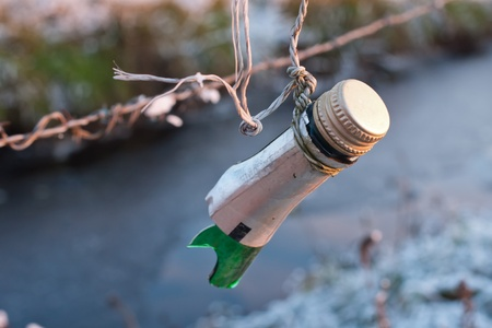 harming: part of a bottle attached to a barbed wire