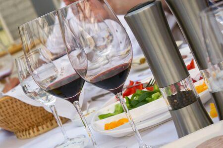 Nahaufnahme zweier Rotweingläser auf gedecktem Tisch mit Salz- und Pfeffermühle Stock Photo