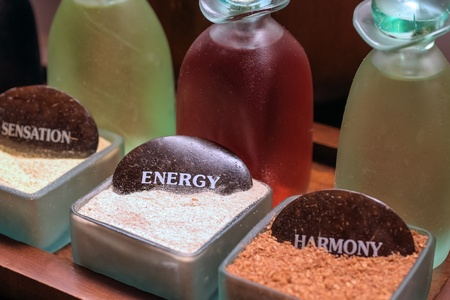 wellness - glass-bottles with different coloured massage-oils and powders for peeling Imagens