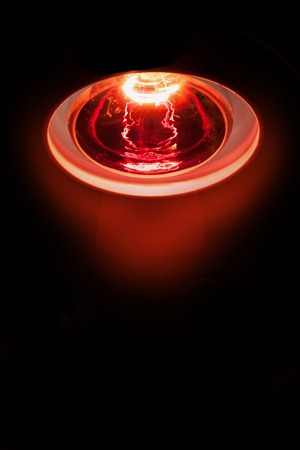 cramping: close-up picture of the shine of a medicinal red-light-lamp with black background Stock Photo