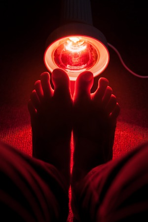 cramping: medicinal red-light-lamp radiating at a womans feet, dark colours Stock Photo