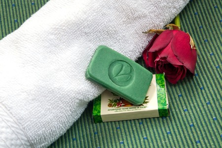 cachet: Stilllife with ayurvedic herbal soap with cachet Green Leaf, red rose and towel