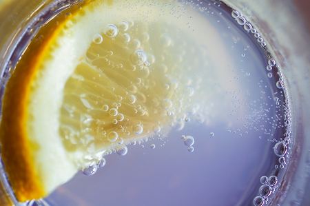longdrink: Closeup view from above of a slice of lemon in a sparkling beverage