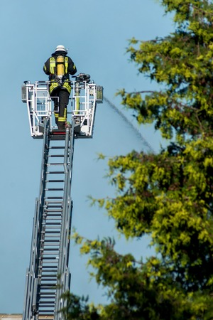 fireman with helmet on the big ladder is clearing fire photo