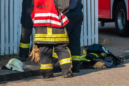 emergency vest: legs of three firemen after an operation Stock Photo