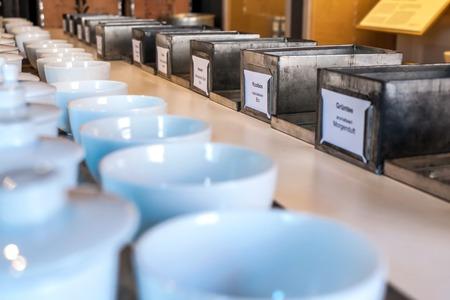 Close-up foto van een reeks van metalen blikjes met verschillende soorten thee en witte kommen