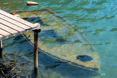 Old rowing boat sunken under water at a wooden jetty Imagens